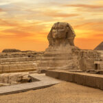 Landscape with Egyptian pyramids, Great Sphinx and silhouettes Ancient symbols and landmarks of Egypt for your travel concept to Africa in golden sunlight.